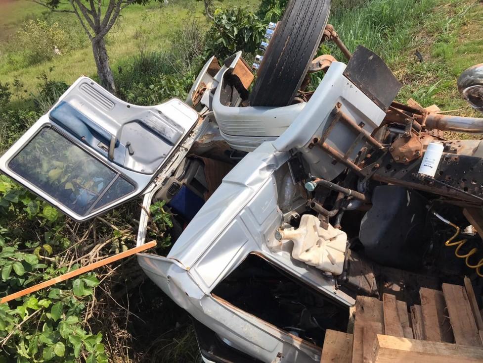 Condutor fica preso às ferragens após carreta com madeira tombar